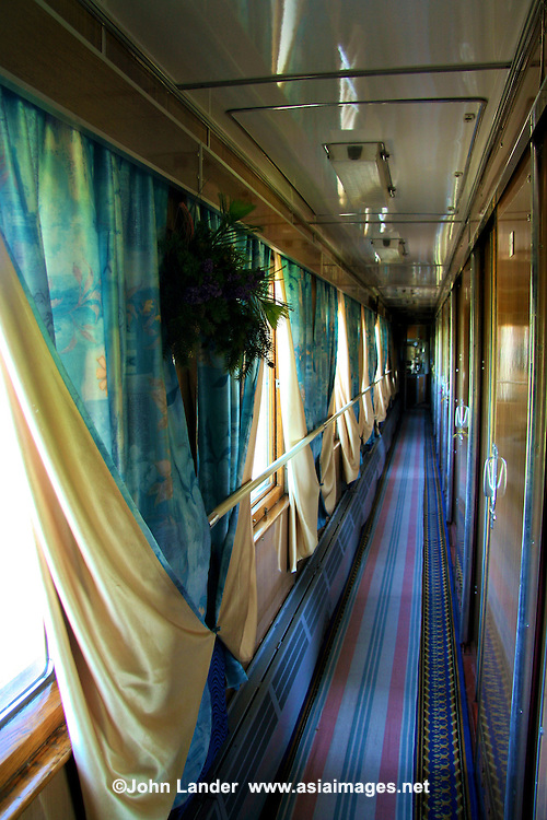"The blue-and-white theme on ""The Baikal"" continues to its corridors.  The provinitsas keep the water boiling at the end of each corridor, the carpets vacuumed and the windows locked.  Though everyone requests, at one time or another, that the windows be opened usually towards the end of the journey when smells are getting ripe, the attendants are loathe to open them.  In part, this is for the sake of security and guarding against unauthorized entry and theft.  However, it is to preserve the unholy air-conditioning that wafts down the corridors and through the compartments, except in stations when it shuts off.  This is when passengers most loudly request that the windows be opened, in addition to the photographers on board who always want at least one to be open."