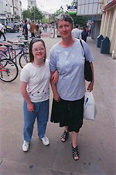 Mother standing in street with teenage daughter with Downs Syndrome,
