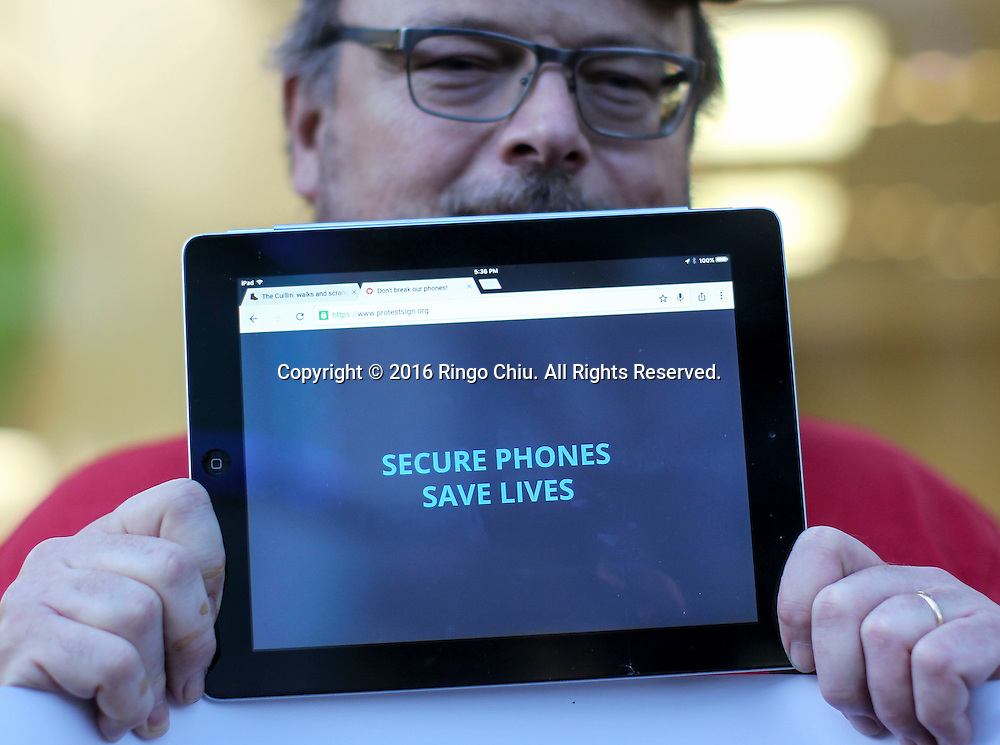 A demonstrator hold up his iPad during a rally in support of data privacy outside the Apple store, Tuesday, Feb. 23, 2016, in Los Angeles. Protesters assembled in more than 30 cities around the world to lash out at the FBI for obtaining a court order that requires Apple to make it easier to unlock an encrypted iPhone used by a gunman in December's mass murders in California.(Photo by Ringo Chiu/PHOTOFORMULA.com)<br /> <br /> Usage Notes: This content is intended for editorial use only. For other uses, additional clearances may be required.