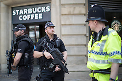 © Licensed to London News Pictures . 25/05/2017 . Manchester , UK . Armed police outside a branch of Starbucks on St Ann's Square in Manchester City Centre after a minute's silence is held in St Ann's Square in Manchester City Centre , following a terrorist attack at an Ariana Grande concert at Manchester Arena that killed twenty two people . Photo credit: Joel Goodman/LNP