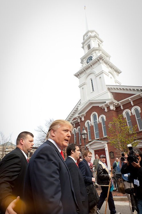 Donald Trump walks in front of North Church in Market square Portsmouth, NH. Real Estate Mogul, TV Star and Presidential hopeful Donald Trump makes a visit to Portsmouth, NH for meetings and a meet and greet as he walks around Downtown Portsmouth.