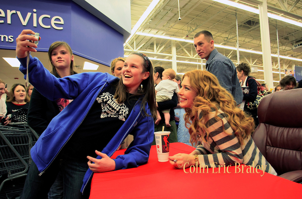 Twelve-year-old Lexi Thompson of South Jordan, Utah takes a picture with Twilight star Rachelle Lefevre, right, who plays the character Victoria, during an autography session for fans at the Walmart store in Riverton, Utah during the midnight DVD movie release event March 21, 2009. (AP Photo/Colin Braley)