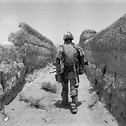 "A Canadian soldier walks up a narraow path between mud walls on what is known as ""Route Nightmare"" in a village in Panjwaii District, Kandahar, Afghanistan. The mud walls and unpaved paths and roads due to lack of development and reconstruction in almost all of the impoverished rural areas of Kandahar allows for the easy planting of land mines and road side bombs by insurgents. (Credit Image: © Louie Palu/ZUMA Press/The Alexia Foundation).June 20, 2010.Photograph taken on film exact date estimated and not known....."