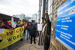 London, UK. 29 October, 2019. A woman exiting the building shows support for outsourced workers belonging to the United Voices of the World (UVW) trade union protesting outside the office of the Chief Executive of Imperial College Healthcare NHS Trust Professor Tim Orchard at St Mary's Hospital Paddington. Around 200 migrant cleaners, porters and caterers outsourced via Sodexo, one of the world's largest multinational corporations, are striking for equal pay, conditions and treatment with broadly equivalent NHS colleagues who are paid £6,000-10,000 p.a. more and have scheduled 12 days of strike action.