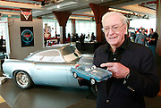 In this photo from Disney, actor Michael Caine, voice of new Cars 2 British agent Finn McMissile, holds one of the more than 300 new Cars  2 toys releasing in May, in front of a life-sized replica at a Toy Fair press event in New York, Monday, Feb. 14, 2011. ( AP Photo/Disney/Stuart Ramson)