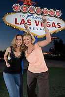 Two women toasting in front of Welcome to Las Vegas sign