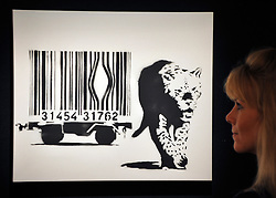 © Licensed to London News Pictures. 23/03/2012. London, UK. A member of Bonham's staff looks at one of the highlights of the Urban Art Sale, Banksys Leopard and Barcode, acquired directly from an exhibition entitled Existencilism at the 33 1/3 Gallery, Los Angeles by the present owner, which has never before been seen at auction and has attracted a pre-sale estimate of £60,000  80,000. A photocall of Bonham's Urban Art Sale including Seventeen art works by the celebrated graffiti artist, Banksy, which are to be sold at Bonhams, London, ahead of the Urban Art Sale, which takes place on 29 March 2012. . Photo credit : Stephen SImpson/LNP