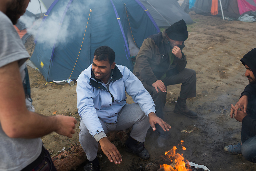 Refugees warm themselves arounda  fire on the morning of March 8, 2016 on the Macedonian (FYROM) border in Idomeni, Greece.
