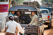 09 MARCH 2013 - ALONG HIGHWAY 13, LAOS:  People in the back of a songthaew (pickup truck converted to bus) in a construction zone on Highway 13 in the province of Vientiane in Laos. The paving of Highway 13 from Vientiane to near the Chinese border has changed the way of life in rural Laos. Villagers near Luang Prabang used to have to take unreliable boats that took three hours round trip to get from the homes to the tourist center of Luang Prabang, now they take a 40 minute round trip bus ride. North of Luang Prabang, paving the highway has been an opportunity for China to use Laos as a transshipping point. Chinese merchandise now goes through Laos to Thailand where it's put on Thai trains and taken to the deep water port east of Bangkok. The Chinese have also expanded their economic empire into Laos. Chinese hotels and businesses are common in northern Laos and in some cities, like Oudomxay, are now up to 40% percent. As the roads are paved, more people move away from their traditional homes in the mountains of Laos and crowd the side of the road living off tourists' and truck drivers.    PHOTO BY JACK KURTZ