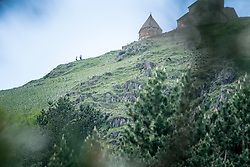 14 June 2016, Kazbegi (Stepantsminda), Georgia: Hikers walking up the mountainside to the 14th century Holy Trinity Church, also known as Gergeti Trinity Church, located on a hilltop near the dormant stratovolcano of Mount Kazbek.