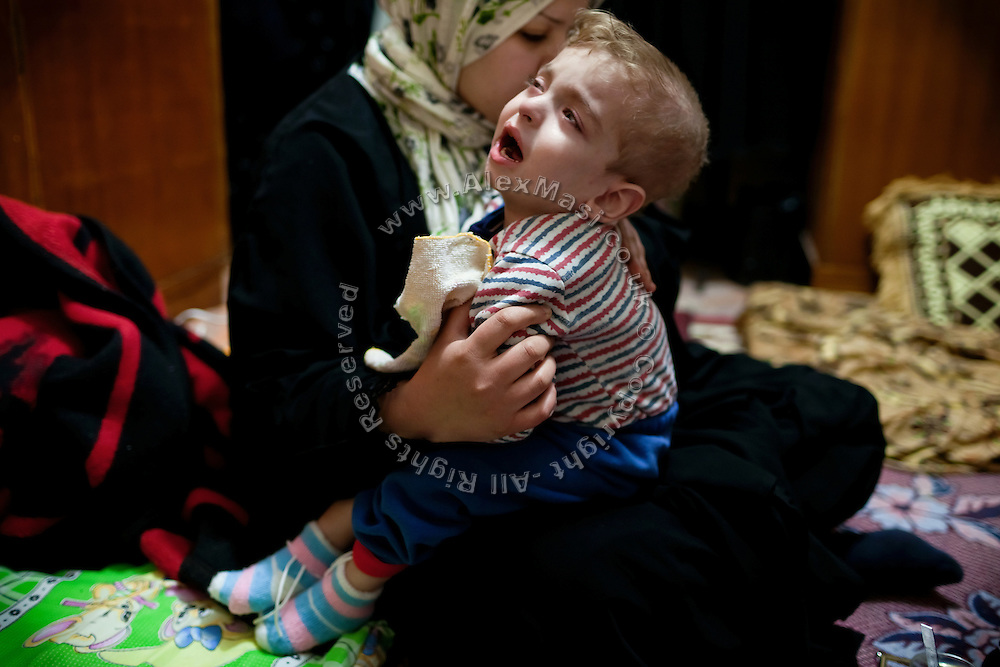 Saadi Othman, 3, a boy suffering from a severe brain damage, blindness and paralysis, is being comforted by his mother while having breakfast in their home in Fallujah, Iraq. The parents and their relatives have no history of birth defects.