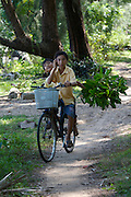Phu Quoc Island. Bai Thom. Boys with a branch on a bicycle.