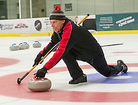 """Four Sheets to the Wind"" Chris Miller slides his stone during Thursday night's Curling League at the Plymouth State University Ice Arena.  (Karen Bobotas/for the Laconia Daily Sun)"