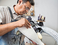 Male worker buffing prosthetic limb