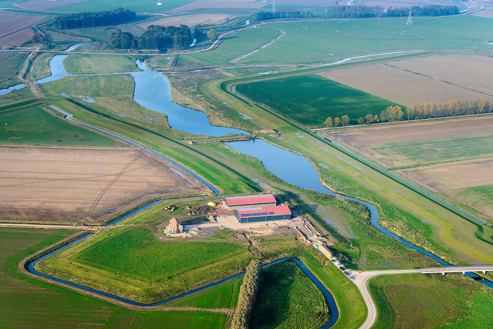 Nederland, Noord-Brabant, Werkendam, 28-10-2014; Ruimte voor de Rivier project Ontpoldering Noordwaard. Nieuwe boerderij op terp.<br /> De Noordwaard wordt ontpolderd door de dijken aan de rivierzijde gedeeltelijk af te graven, hierdoor kan de Nieuwe Merwede bij hoogwater via de Noordwaard sneller naar zee stromen. Gevolg van de ingrepen is ook dat de waterstand verder stroomopwaarts zal dalen.<br /> National Project Ruimte voor de Rivier (Room for the River) By lowering and / or moving the dike of the Noordwaard polder the area will become subject to controlled inundation and function as a dedicated water detention district. Houses and farmhouses will be constructed on new dwelling mounds. <br /> luchtfoto (toeslag op standard tarieven);<br /> aerial photo (additional fee required);<br /> copyright foto/photo Siebe Swart