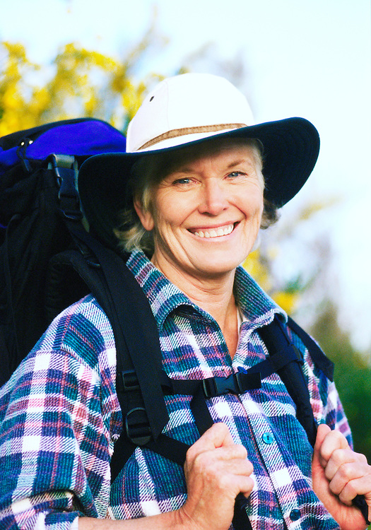 Portrait of a smiling senior woman with a backpack on.