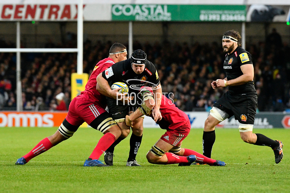 Thomas Waldrom of Exeter Chiefs is tackled by two Harlequins players during the Aviva Premiership match between Exeter Chiefs and Harlequins at Sandy Park, Exeter, United Kingdom on 19 November 2017. Photo by Graham Hunt.