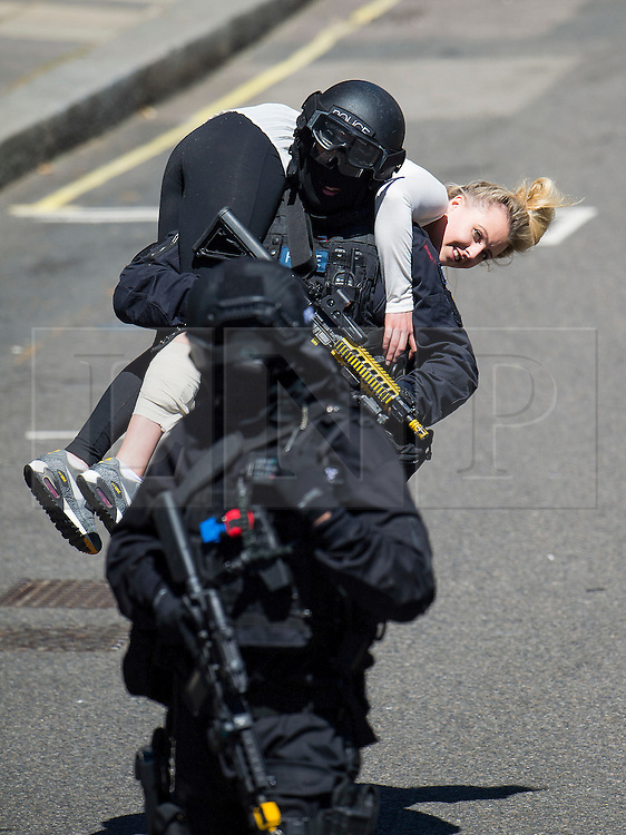 © Licensed to London News Pictures. 30/06/2015. London, UK. Armed police on the scene helping people with injuries. Members of the emergency service take part in a mocked-up terrorist firearms attack at Aldwych station in central London. The exercise is the biggest to take place in London and is happening a week after dozens of people where killed when a gunman opened fire on a beach in Tunisia.  Photo credit: Ben Cawthra/LNP
