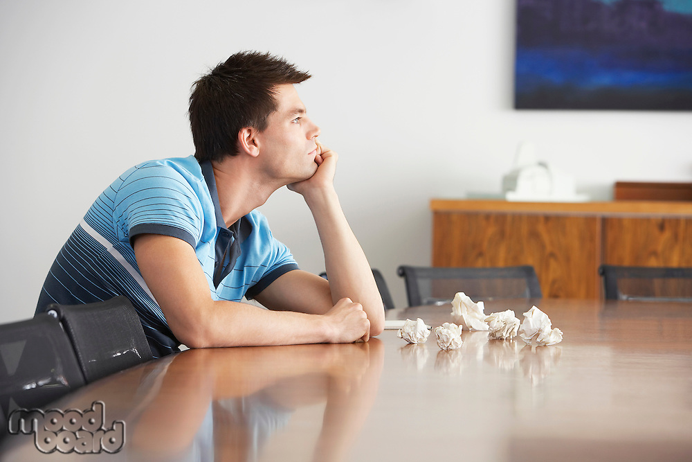 Frustrated Man sitting at conference table With Crumpled Paper side view