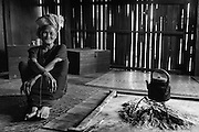 Myanmar. Woman and hearth of the first floor of a farm house. <br /> Traditionaly built bamboo farm house - Shan State.