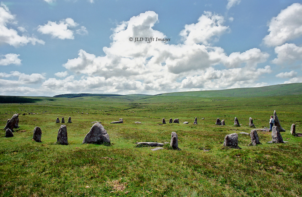 Stone circle, Dartmoor.  Figure of a young man leans agaisnt one of the upright stones.  Landscape of wide expanse of moor and sky.