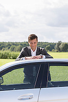 Portrait of young businessman leaning on broken down car at countryside