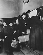 Immigrants arriving in America, photograph, 1908, by Lewis Hine, displayed in the Ellis Island Immigration Museum, in the main building on Ellis Island, the immigration processing centre for the United States from 1892 to 1954, at the mouth of the Hudson river in New York City, NY, USA. Ellis Island and its Immigration Museum are part of the Statue of Liberty National Monument and are managed by the National Park Authority. Picture by Manuel Cohen