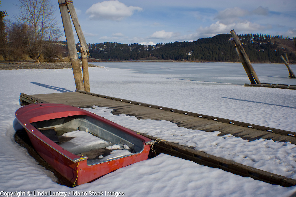 A swamped boat at Lake Chatcolet sit high and dry on the snow covered lake bed duting low water in winter. Heyburn State Park, Idaho, USA