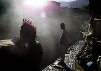 Anne-Rose, habitante de los suburbios de Puerto Principe, izquierda, toma su desayuno antes de comenzar a vender carbon vejetal, las clases mas pobres tienen esperanza en el presidente electo Jean-Bertrand Aristide, quien tomara el poder manana en horas de la manana, 6 de Febrero del 2001, Puerto Principe, Haiti, (AP Photo/Cristobal Herrera)