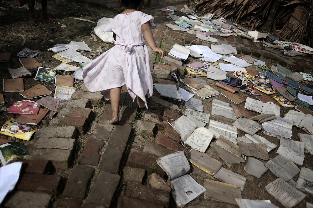 A young girl from the village of Chaung Lin runs next to wet books drying, to receive food thrown from a boat on May 23, 2008 in the isolated area of Kanzeik in the Irrawaddy Delta region -- an area only accessible by boat which has received neither government nor foreign aid. Voters in regions devastated by the cyclone, many hungry and destitute, cast ballots on May 24 in a referendum that many said was meaningless because Myanmar's junta has already declared victory.