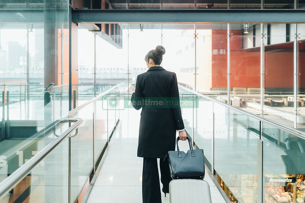 February 24, 2017 - Businesswoman using mobile and pulling trolley luggage, Milan, Italy (Credit Image: © Eugenio Marongiu/Image Source via ZUMA Press)