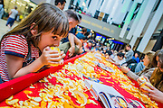 People peel oranges and then drink the juice from the cored fruit at the Groundnut Table - in a traditional West African method. The Turbine Festival 2015 - One City One Day - sponsored by Hyundai. The festival includes many activities for all ages exploring art and technology.