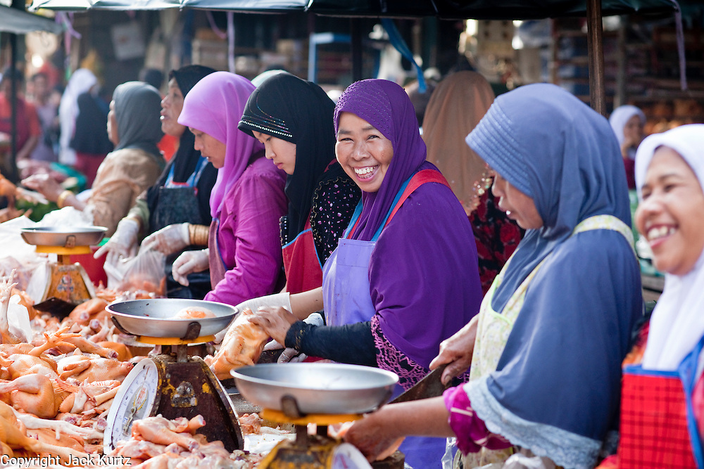 "Sept 25, 2009 -- PATTANI, THAILAND: Muslim women butcher chickens for customers in the morning market in Pattani, Thailand. Thailand's three southern most provinces; Yala, Pattani and Narathiwat are often called ""restive"" and a decades long Muslim insurgency has gained traction recently. Nearly 4,000 people have been killed since 2004. The three southern provinces are under emergency control and there are more than 60,000 Thai military, police and paramilitary militia forces trying to keep the peace battling insurgents who favor car bombs and assassination.  Photo by Jack Kurtz / ZUMA Press"