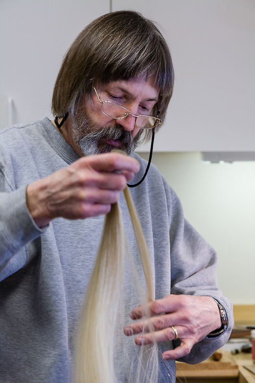 Beekman selecting horsehair from a hank to use to restring a bow.