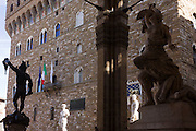 David and Hercules & Cacus statue copies and Palazzo Vecchio in Piazza della Signoria..Benvenuto Cellini's Perseus with the Head of Medusa, Michelangelo's David Hercules and Cacus statues and Palazzo Vecchio in Piazza della Signoria. The Loggia dei Lanzi, also called the Loggia della Signoria, is a building on a corner of the Piazza della Signoria in Florence, Italy, adjoining the Uffizi Gallery. It consists of wide arches open to the street, three bays wide and one bay deep. The arches rest on clustered pilasters with Corinthian capitals.