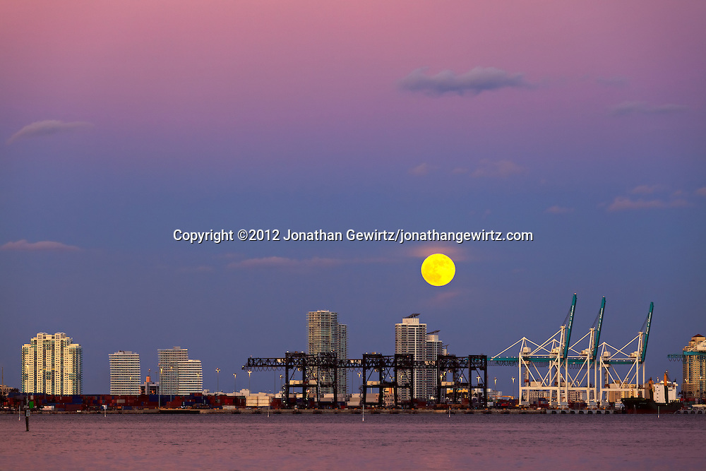 The full moon rises over the Port of Miami, Florida and Miami Beach condo buildings in the background on October 29, 2012. WATERMARKS WILL NOT APPEAR ON PRINTS OR LICENSED IMAGES.