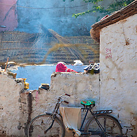 A Bicycle with Draped Cloth Sits in A Yard as Woman Cooks in the Background In Pushkar, Rajasthan, India