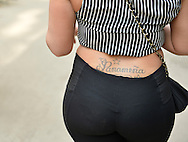 NYC, New York, U.S.  21st May 2013.  This woman, with a tattoo 'Panameña'  on the back of her waist, is walking in Manhattan during a pleasant spring day, with a high of 86ºF/32ºC,