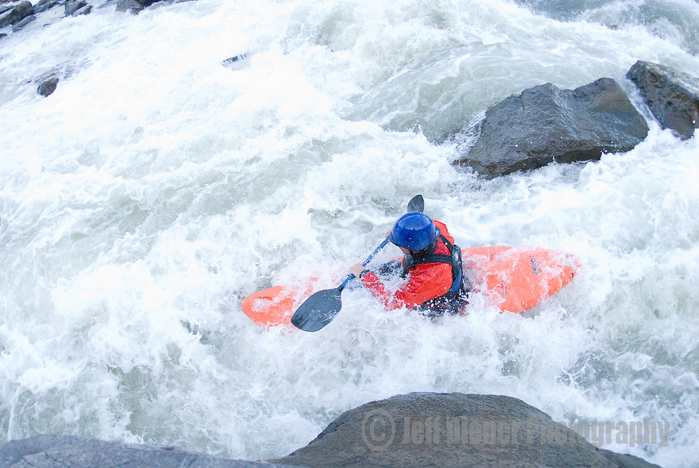 A young man kayaks the whitewater on the Teton River in eastern Idaho.