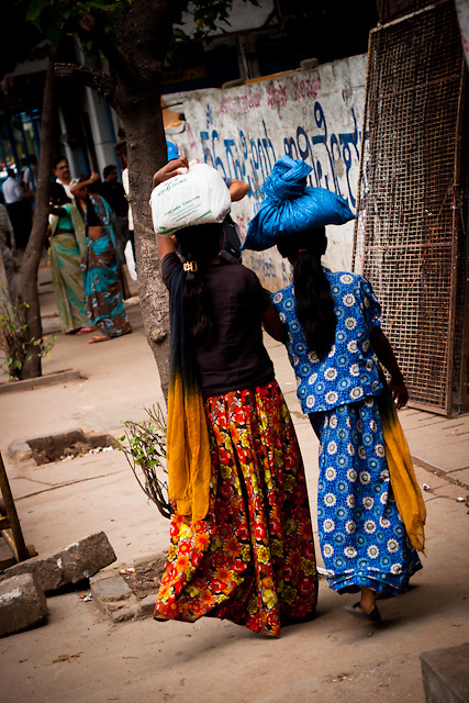 Two women walking along Old Airport Road in Bangalore, India. The women are wearing traditional Indian Sari's carrying goods on their heads.
