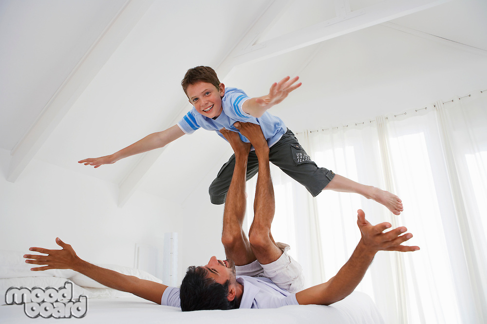 Son balancing on father's legs on bed in bedroom