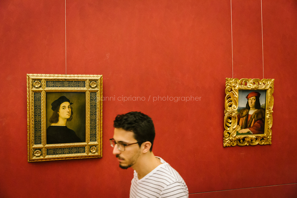 FLORENCE, ITALY - 3 JUNE 2018: A visitor walks by (L-R) &quot;Self-Portait&quot; (1504-1506 ca) and &quot;Portrait of a Young Man with an Apple&quot; (1504-1505 ca) by Raphael here at the Uffizi before being relocated at Palazzo Pitti, in Florence, Italy, on June 3rd 2018.<br /> <br /> As of Monday June 4th 2018, Room 41 or the &ldquo;Raphael and Michelangelo room&rdquo; of the Uffizi is part of the rearrangement of the museum's collection that has<br /> been defining Uffizi Director Eike Schmidt&rsquo;s grander vision for the Florentine museum.<br /> Next month, the museum&rsquo;s Leonardo three paintings will be installed in a<br /> nearby room. Together, these artists capture &ldquo;a magic moment in the<br /> first decade of the 16th century when Florence was the cultural and<br /> artistic center of the world,&rdquo; Mr. Schmidt said. Room 41 hosts, among other paintings, the dual portraits of Agnolo Doni and his wife Maddalena Strozzi painted by Raphael round 1504-1505, and the &ldquo;Holy Family&rdquo;, that Michelangelo painted for the Doni couple a year later, known as the<br /> Doni Tondo.