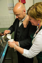 Pictured: Bonnie Burton watches carefully as Patrick Harvie makes a latte<br /> <br /> Greens co-cordinator Partrick Harvie headed to Rose Street in Edinburgh today to serve customers at Social Bite cafe, a social enterprise supporting the homeless<br /> <br /> Ger Harley | EEm 20 April 2016