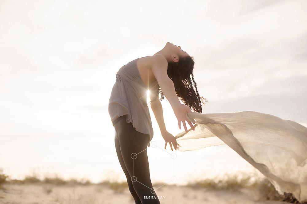 A joyful woman's scarf blowing in the desert breeze.