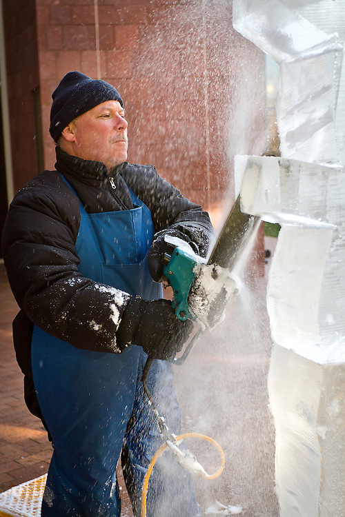 Ice sculptor Bill Gordish focuses intently on making precise cuts while sculpting an 8' tall beverage luge for the Festival of Ice on Wednesday afternoon in the courtyard of the JRC..