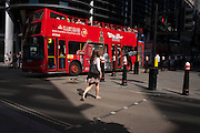 A tour bus makes it way along Cannon Street in the City of London, UK.