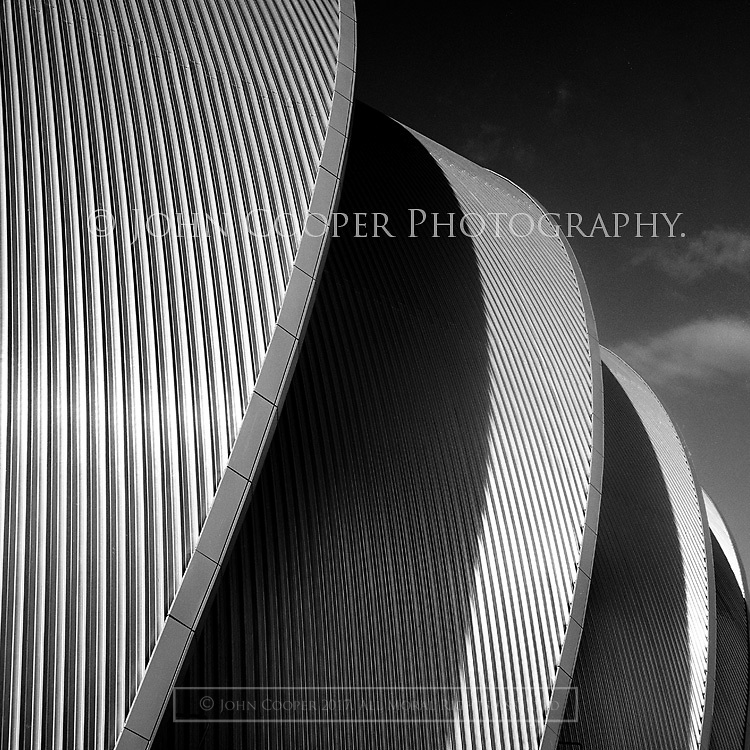 Black and white architectural photograph of the Clyde Auditorium in Glasgow. Affectionately know as 'The Armadillo'. Designed by architect, Sir Norman Foster. Mounted print available to purchase.