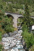 Arched stone train bridge over a stream in Lavin is a municipality in the district of Inn in the Swiss canton of Graubünden