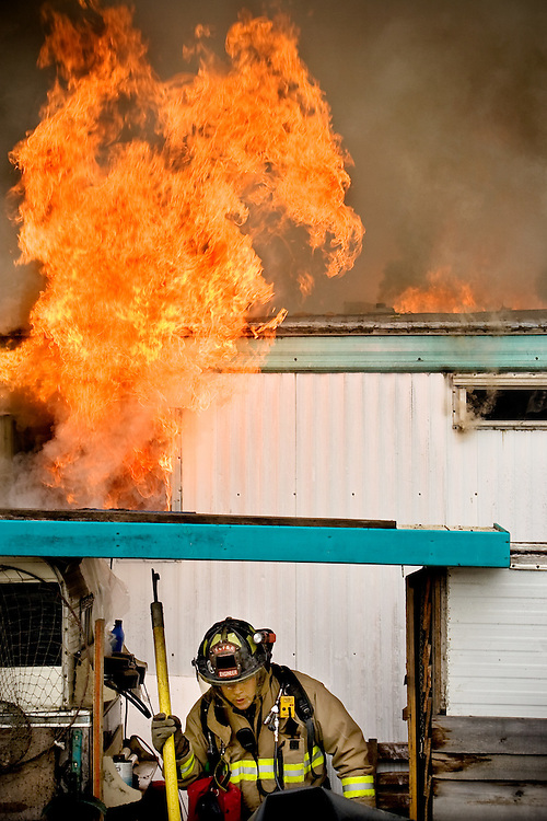 JEROME A. POLLOS/Press..A Kootenai County firefighter retreats from the backside of a mobile home after breaking windows for ventilation during a fire Thursday in Post Falls.
