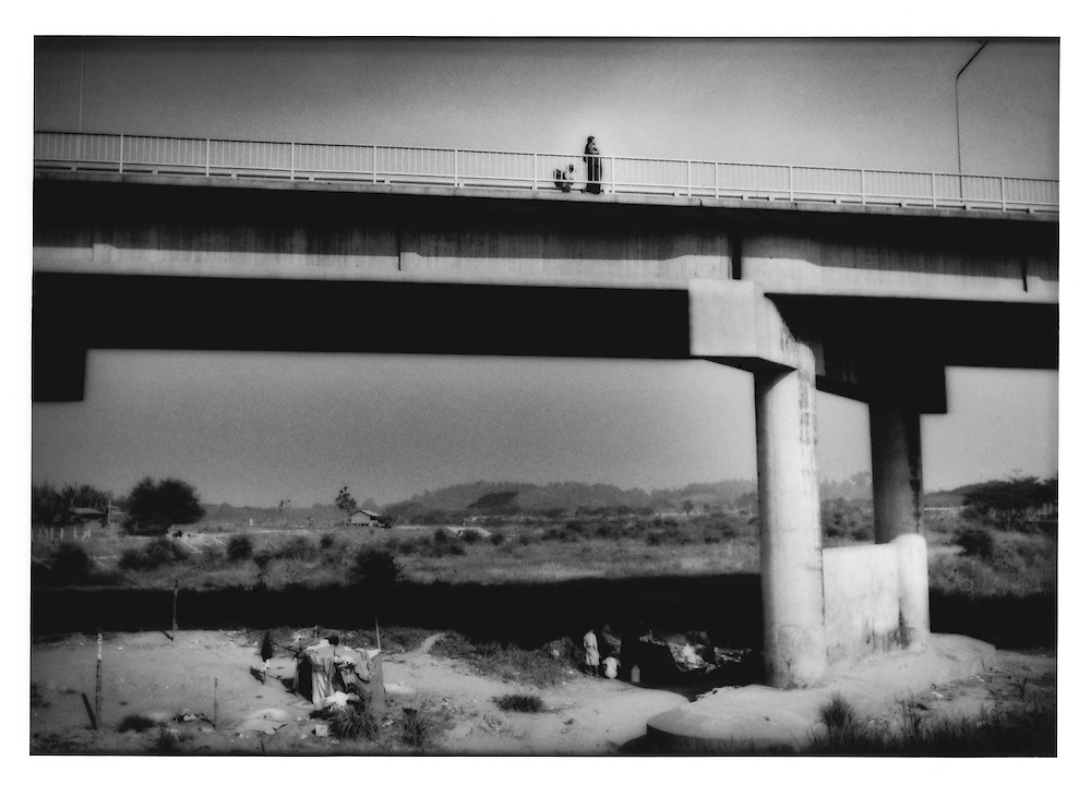 People walking into Thailand on Thai-Myanmar Friendship Bridge from Myawaddy, Burma (Myanmar) while Burmese merchants squat beneath the bridge on the Thai side of the Mae Nam Moei River, Mae Sot, Thailand.